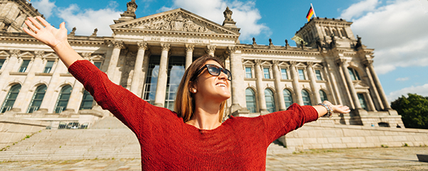 An Overview of Living in Germany - An image of a cheerful woman outside of a large building near Bun