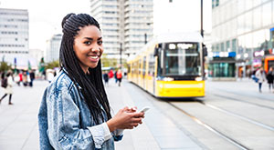 Transport Options in Germany - An image of a young woman walking in Berlin, Germany with a tram in t