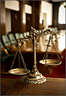 Law jobs - scales of justice with courtroom background