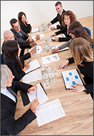 Management jobs - business men and women round an oblong table