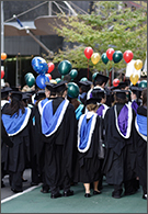 Masters degree - graduates marching in robes with balloons