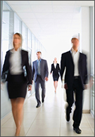Professional jobs - blurred image of  busy office workers walking in hallway