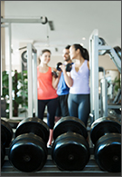 Sport and Leisure jobs - three people in gym near weightlifting equipment